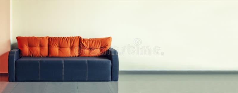 Kanapa, wewnętrzny projekt, biuro Pusta poczekalnia z nowożytną błękitną kanapą z kolor żółty poduszkami przed drzwi i zegarem da obrazy royalty free