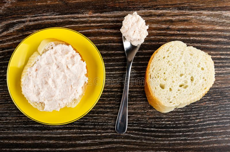 Kanapka z krill pastą w spodeczku, łyżka z pastą, kawałek chleb na drewnianym stole Odg?rny widok zdjęcia royalty free