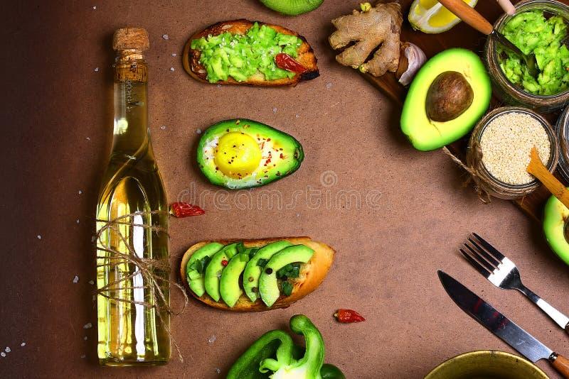 Kanapki, bruschetta z avocado, Zieleni warzywa pieprzą, cytryna, imbir, czosnek, olej, morze sól, rucola sałatka, butelki oliwa z fotografia royalty free