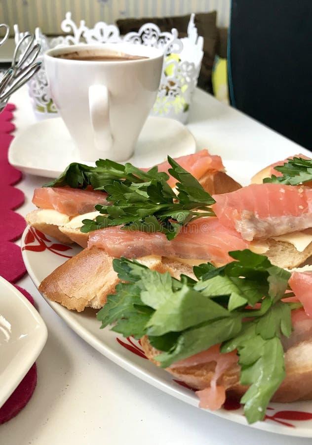 Kanapki z łososiem i zieleniami Kawałki ryba kłaść na chlebowym baguette, oliwiącym Dekorujący z świeżą pietruszką obrazy royalty free
