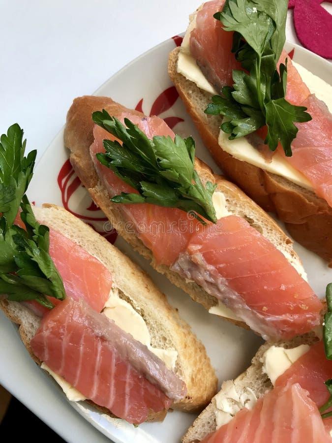 Kanapki z łososiem i zieleniami Kawałki ryba kłaść na chlebowym baguette, oliwiącym Dekorujący z świeżą pietruszką obraz royalty free