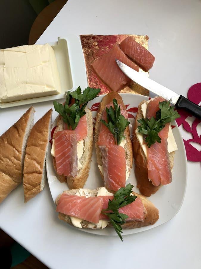 Kanapki z łososiem i zieleniami Kawałki ryba kłaść na chlebowym baguette, oliwiącym Dekorujący z świeżą pietruszką fotografia royalty free