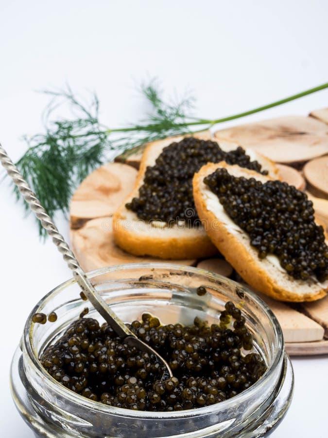 Kanapki z czarnym kawiorem, s?ojem kawior i ?y?k?, Na drewnianym stole fotografia stock