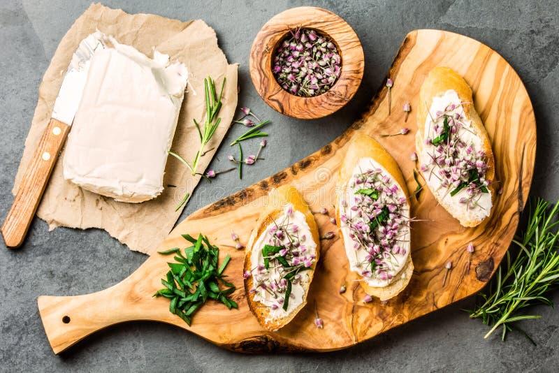 Kanapki z kremowym serem i czosnków jadalnymi kwiatami, oliwki deska obraz royalty free