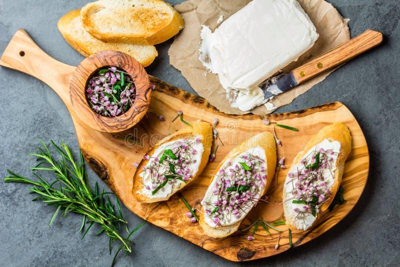 Kanapki z kremowym serem i czosnków jadalnymi kwiatami, oliwki deska zdjęcia royalty free
