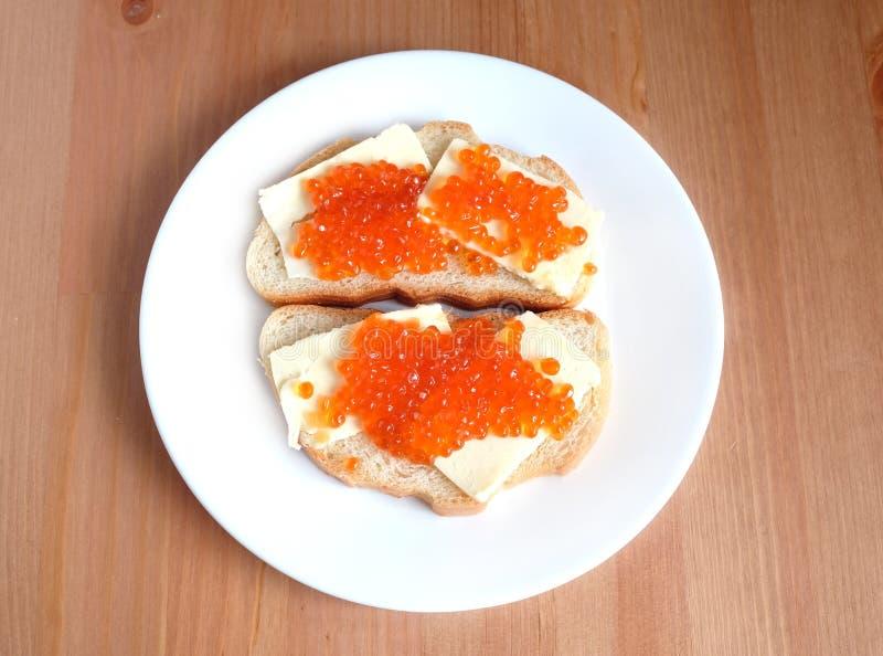 Kanapki z masłem i czerwień kawiorem na białego chleba kłamstwach na białym round talerzu na drewnianym tle fotografia stock
