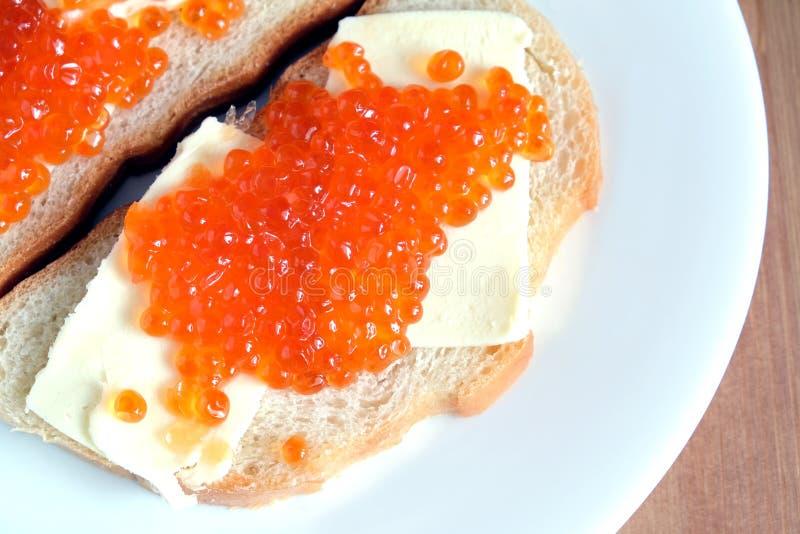 Kanapki z masłem i czerwień kawiorem na białego chleba kłamstwach na białym round talerzu na drewnianym tle obrazy stock