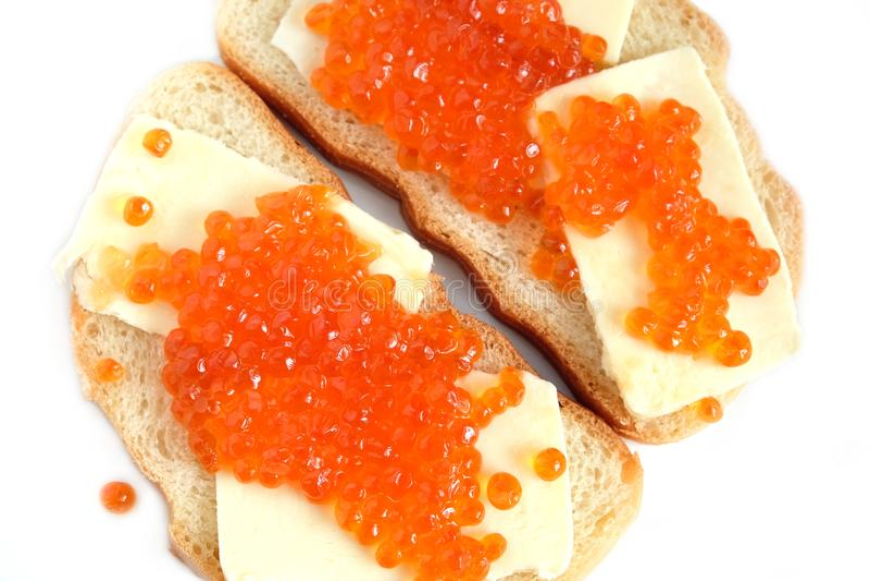 Kanapki z masłem i czerwień kawiorem na białego chleba kłamstwach odizolowywających nad bielem zdjęcia royalty free