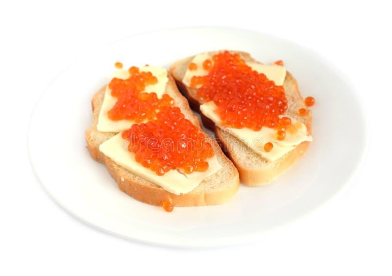 Kanapki z masłem i czerwień kawiorem na białego chleba kłamstwach na round talerzu, odosobniony nadmierny biel obrazy stock