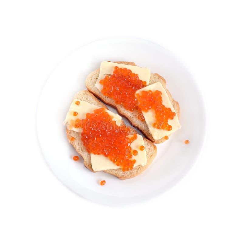 Kanapki z masłem i czerwień kawiorem na białego chleba kłamstwach na round talerzu, odosobniony nadmierny biel obraz royalty free