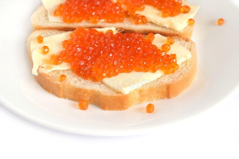 Kanapki z masłem i czerwień kawiorem na białego chleba kłamstwach na round talerzu, odosobniony nadmierny biel fotografia royalty free