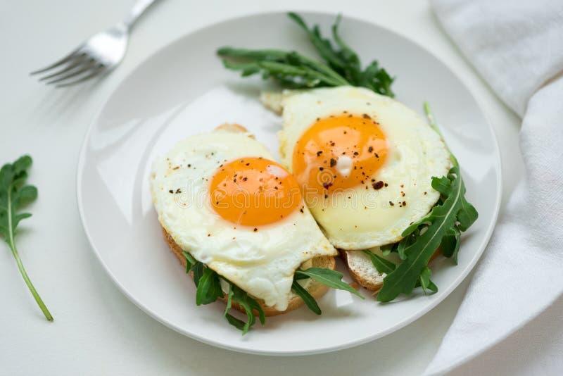Kanapki z ricotta serem, arugula i smażącym jajkiem na białym drewnianym tle, Selekcyjna ostro?? poj?cia zdrowe jedzenie obrazy stock