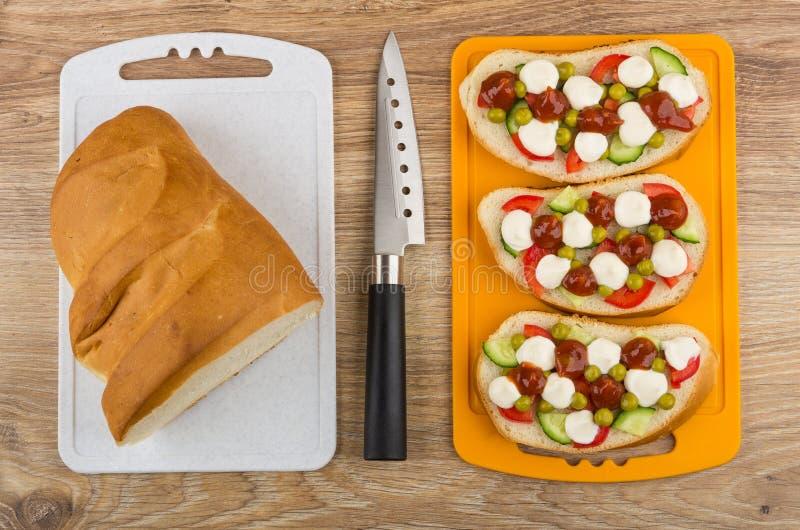 Kanapki z warzywami i majonezem na tnącej desce, brea zdjęcia stock