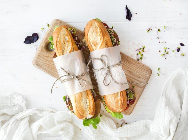 Kanapki z wołowiną, świeżymi warzywami i ziele na nieociosanej drewnianej ciapanie desce, zdjęcie royalty free