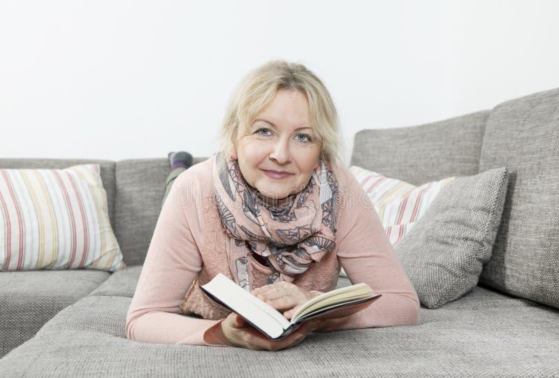 kanapy książkowa czytelnicza kobieta zdjęcie stock