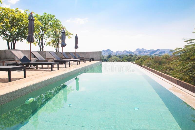 Kanchanaburi, Tailândia - 20 de fevereiro de 2019: Paisagem da piscina superior do telhado com Mountain View no fundo imagens de stock royalty free