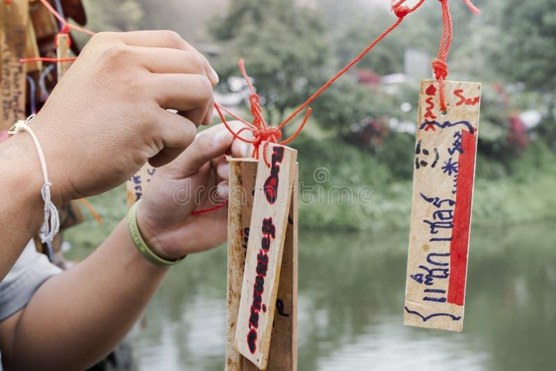 Kanchanaburi, Tailândia - 16 de setembro de 2019: O nome não identificado amarra os cartões de madeira que penduram na ponte fotografia de stock royalty free