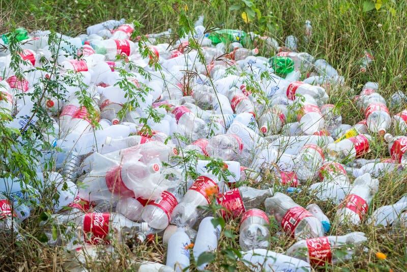 Kanchanaburi, Tailandia - 18 de febrero de 2016: Coca-Cola del refresco de la descarga de basura y agua potable en el patio trase fotos de archivo