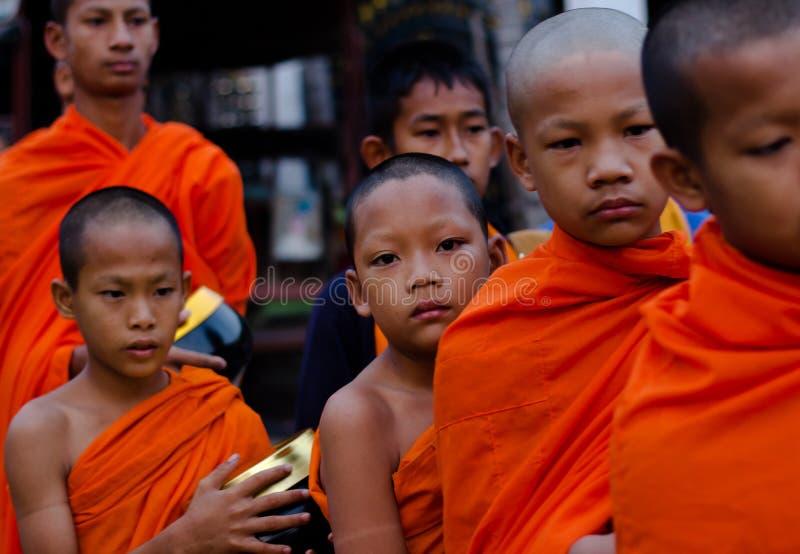 Kanchanaburi, Thaïlande - 16 mars 2014 : Les jeunes moines attendant reçoivent la nourriture des villageois images libres de droits