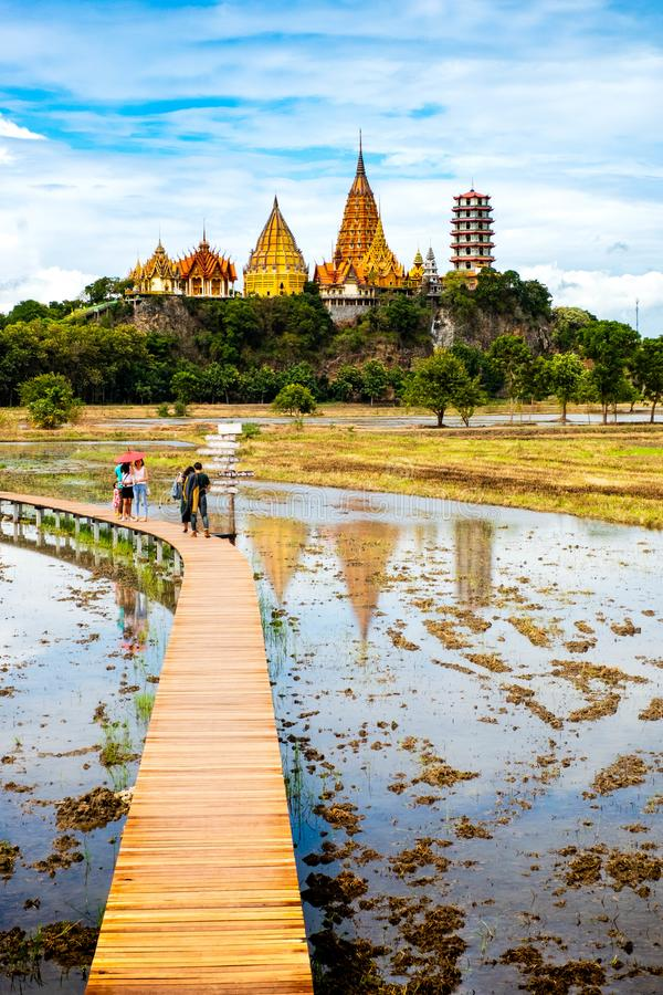 KANCHANABURI THAILAND – August 12, 2018: The Tiger Cave Temple in Tha Muang and Rice field with wooden bridge stock photography