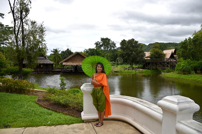 Kanchanaburi, Thailand, 09.09.2019: Beautiful Thai girl in traditional Thai, Siamese dress with green umbrella and accessories in. `Mallika City R.E. 124` a stock photos