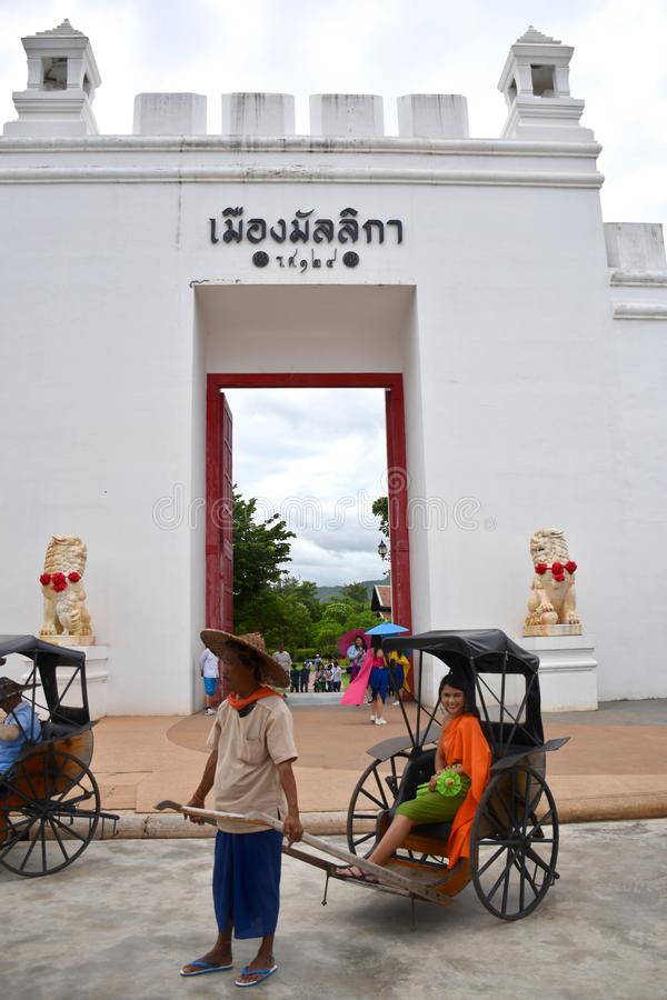 Kanchanaburi, Thailand, 09.09.2019: Beautiful Thai girl in traditional Thai, Siamese dress in an old rickshaw in front of the. Entrance of `Mallika City R.E stock images