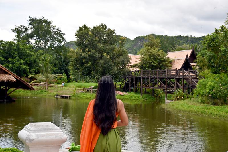 Kanchanaburi, Thailand, 09.09.2019: Beautiful Thai girl in traditional Thai, Siamese dress with green umbrella and accessories in. `Mallika City R.E. 124` a royalty free stock photo