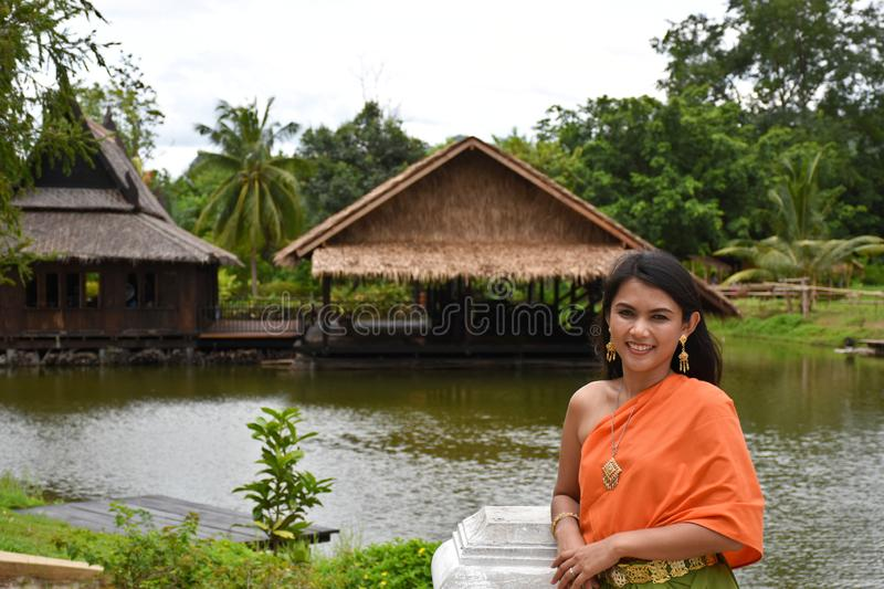 Kanchanaburi, Thailand, 09.09.2019: Beautiful Thai girl in traditional Thai, Siamese dress with green umbrella and accessories in. `Mallika City R.E. 124` a stock photography