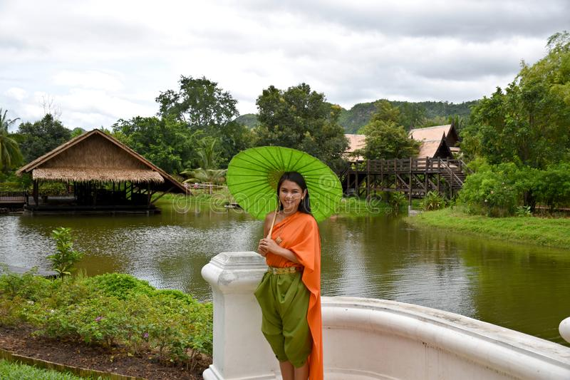 Kanchanaburi, Thailand, 09.09.2019: Beautiful Thai girl in traditional Thai, Siamese dress with green umbrella and accessories in. `Mallika City R.E. 124` a stock images