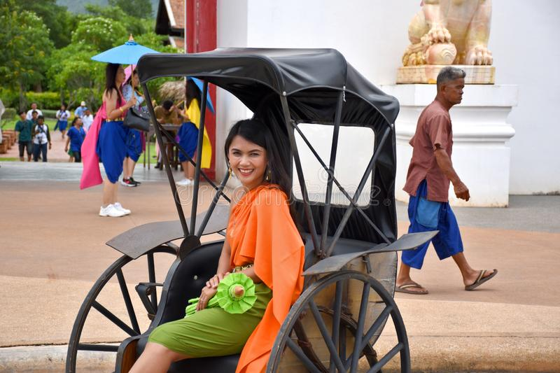 Kanchanaburi, Thailand, 09.09.2019: Beautiful Thai girl in traditional Thai, Siamese dress in an old rickshaw in front of the. Entrance of `Mallika City R.E royalty free stock photos