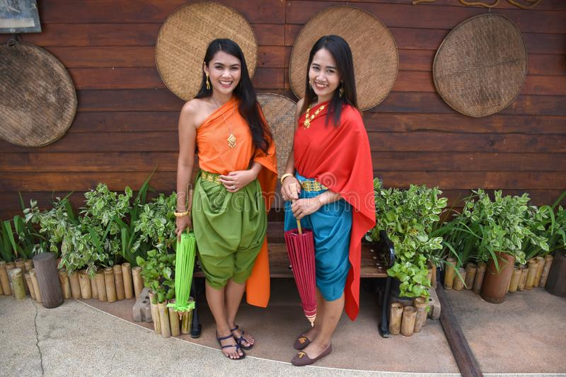 Kanchanaburi, Thailand, 09.09.2019: Beautiful Thai girls in traditional Thai, Siamese dress with green and red umbrellas and. Accessories in `Mallika City R.E stock photography