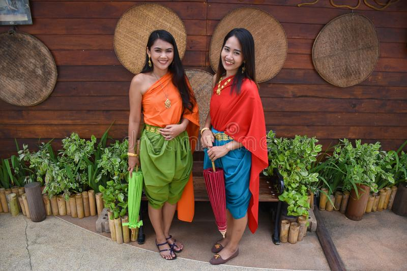 Kanchanaburi, Thailand, 09.09.2019: Beautiful Thai girls in traditional Thai, Siamese dress with green and red umbrellas and. Accessories in `Mallika City R.E royalty free stock photos