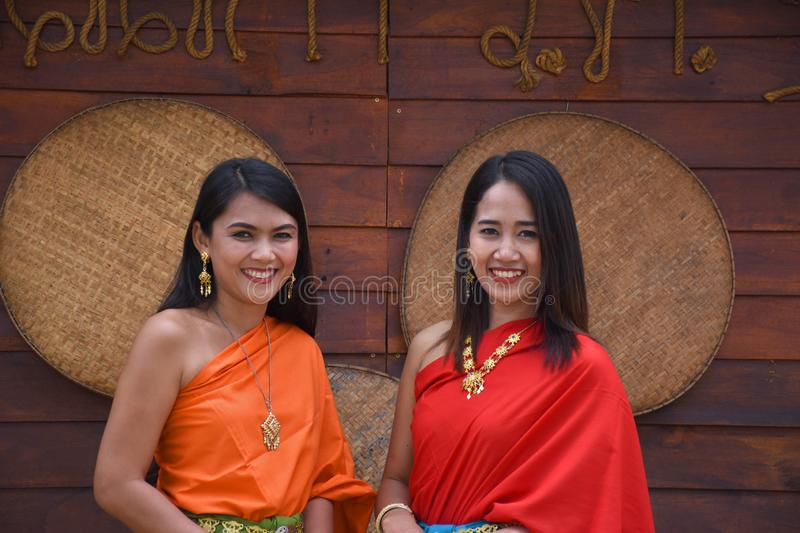 Kanchanaburi, Thailand, 09.09.2019: Beautiful Thai girls in traditional Thai, Siamese dress with green and red umbrellas and. Accessories in `Mallika City R.E royalty free stock photography