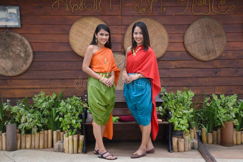 Kanchanaburi, Thailand, 09.09.2019: Beautiful Thai girls in traditional Thai, Siamese dress with green and red umbrellas and. Accessories in `Mallika City R.E stock photo
