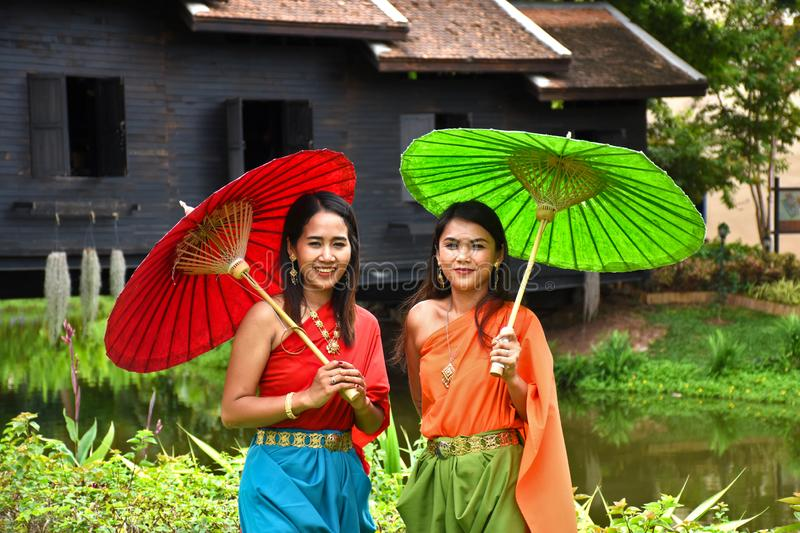 Kanchanaburi, Thailand, 09.09.2019: Beautiful Thai girls in traditional Thai, Siamese dress with green and red umbrellas and. Accessories in `Mallika City R.E stock image