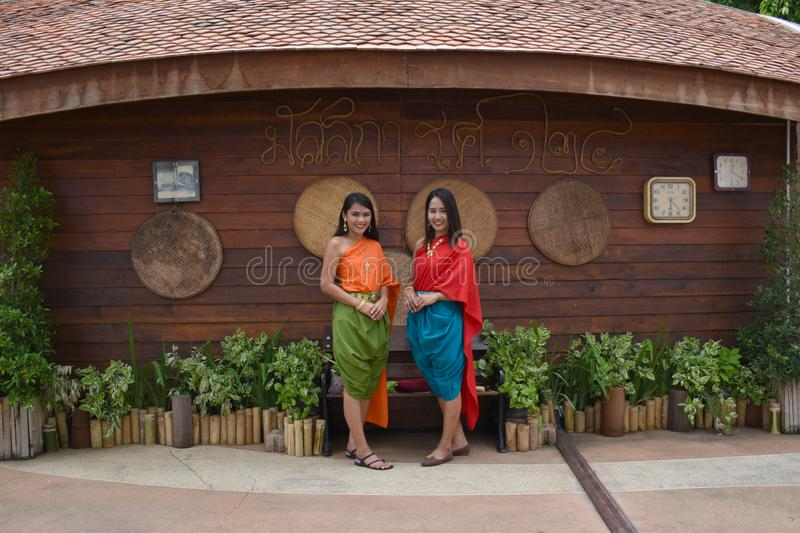 Kanchanaburi, Thailand, 09.09.2019: Beautiful Thai girls in traditional Thai, Siamese dress with green and red umbrellas and. Accessories in `Mallika City R.E stock images