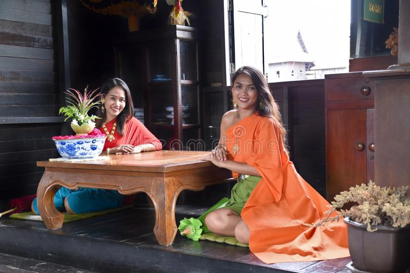 Kanchanaburi, Thailand, 09.09.2019: Beautiful Thai girls in traditional Thai, Siamese dress with green and red umbrellas and. Accessories in `Mallika City R.E stock photos