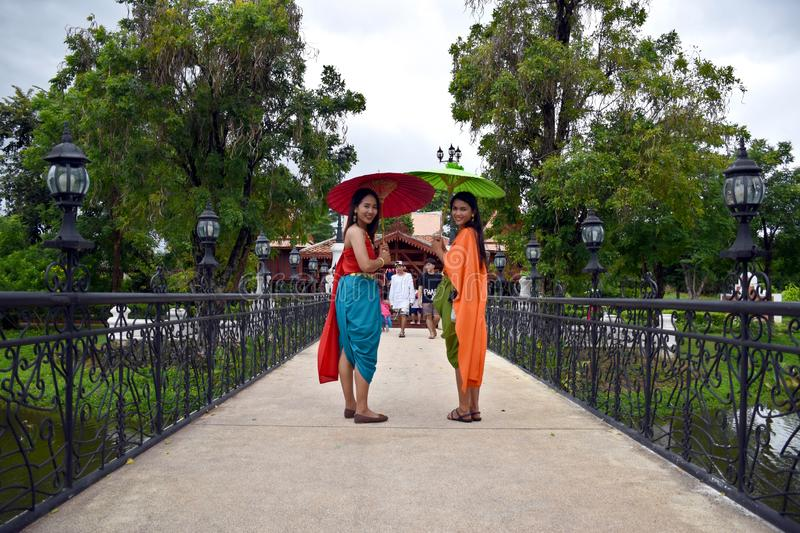 Kanchanaburi, Thailand, 09.09.2019: Beautiful Thai girls in traditional Thai, Siamese dress with green and red umbrellas and. Accessories in `Mallika City R.E royalty free stock photo
