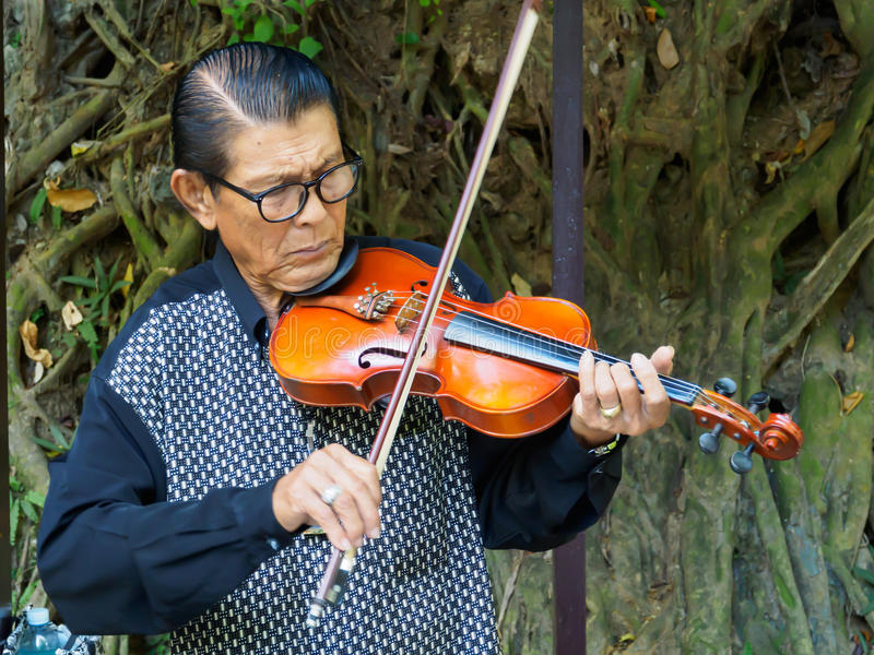 Kanchanaburi, Thailand - December 25,2516 : Asian musician violinist playing violin in public park. royalty free stock images