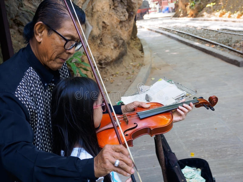 Kanchanaburi, Thailand - December 25,2516 : Asian musician violinist teaching young girl playing violin in public park. stock images