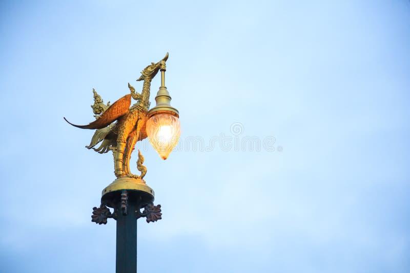 Kanchanaburi, Thailand - December 30, 2018: Golden Swan Sculptural Street Lamp in Thai Contemporary Art glows in twilight on Mon. Bridge in Sangkhlaburi stock photography