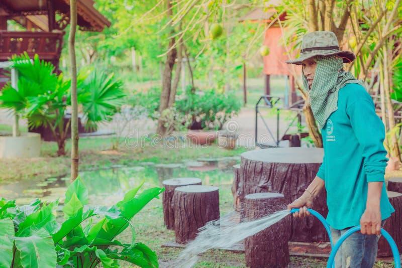 KANCHANABURI-THAILAND, el 2 de marzo de 2019: Del hombre mayor de riego no identificadas con la manguera y trabajo en jardín en  foto de archivo