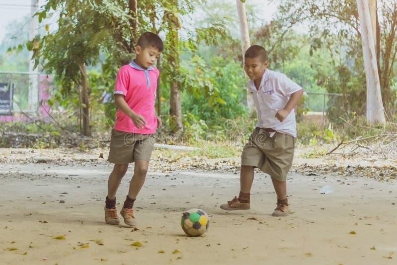 KANCHANABURI THAILAND - FEBRUARI 2: Oidentifierade studenter tycker om att spela gammal fotboll med deras vänner på jordningen i  royaltyfri bild