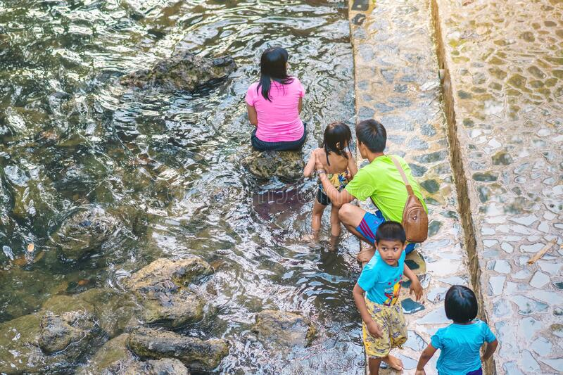 KANCHANABURI, THAILAND - JANUARY 1: Unidentified Asian tourists bathe and soak the body in warm mineral water for good health at stock image
