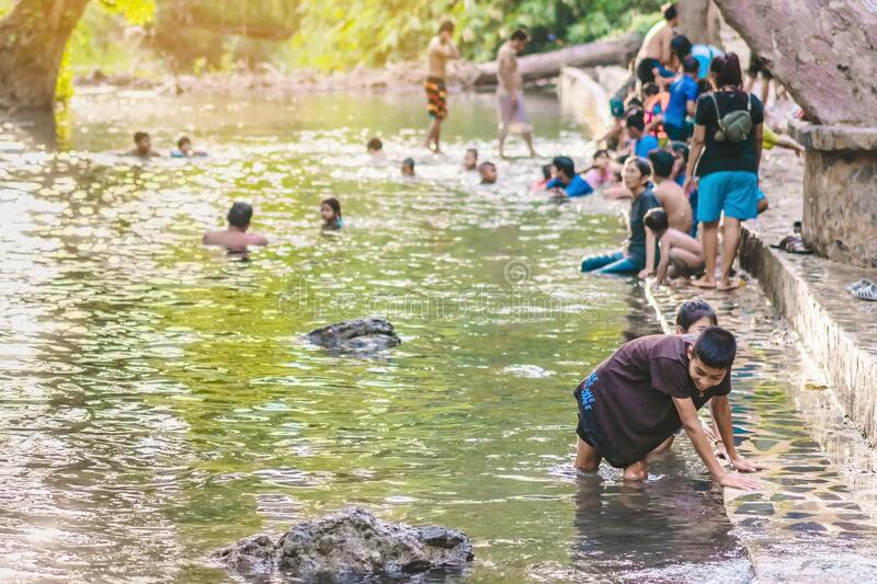 KANCHANABURI, THAILAND - JANUARY 1: Unidentified Asian tourists bathe and soak the body in warm mineral water for good health at stock photography