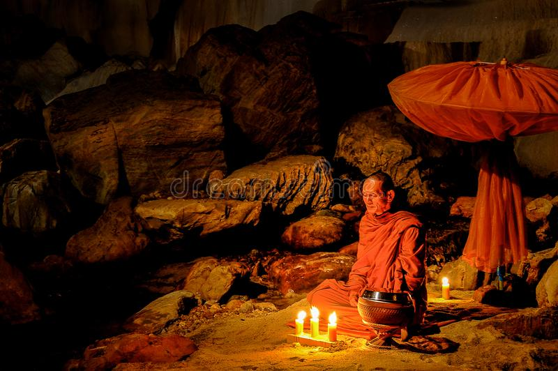 Buddhist monk doing meditation in cave stock photography