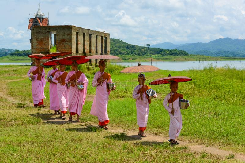 Group of Mon nuns walking out of ruined Buddhist church. Kanchanaburi, Thailand - July 24, 2016: Group of Mon nuns in pink robes holding umbrella walking out of royalty free stock photo