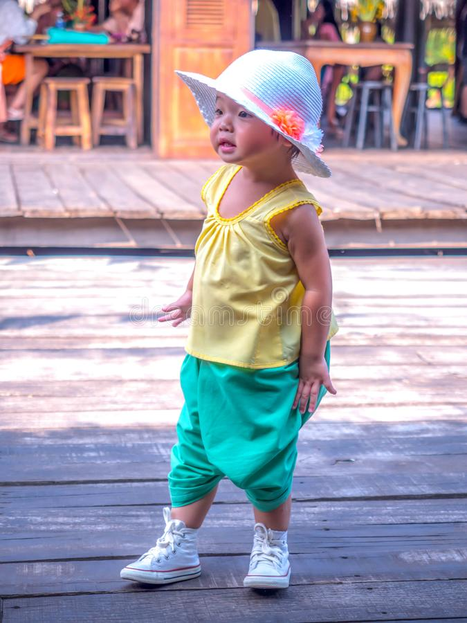 Kanchanaburi Thailand - October 28, 2017: Tourist Little girl wearing traditional thai dress in the old market at Muang Mallika. The new tourist attraction for stock image