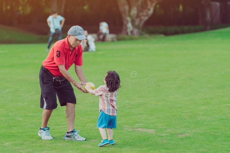 KANCHANABURI THAILAND - OCTOBER 28 :  Unidentified happiness kid and grandfather relaxing by playing ball together at the public stock photography