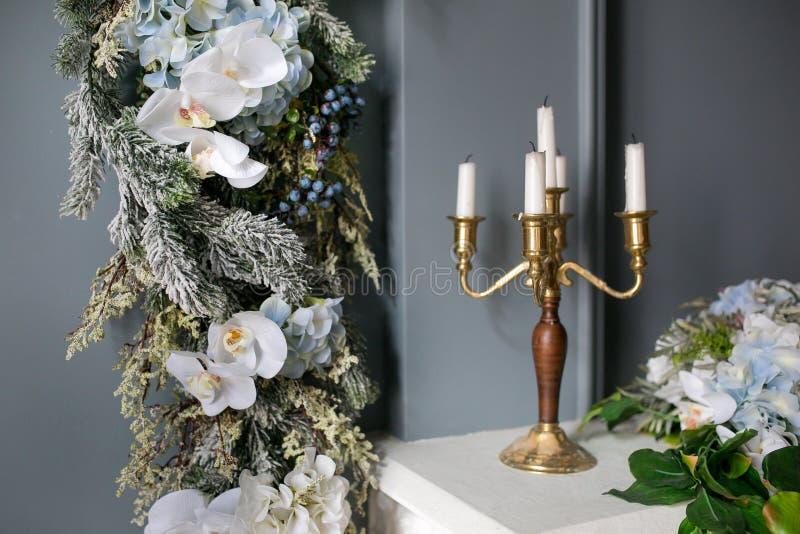 Kandelaar met kaarsen op een witte die open haard met bloemen en spartakken, voor Kerstmis worden verfraaid De ochtend van Kerstm royalty-vrije stock foto